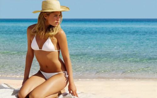 Красивая девушка на песчаном пляже на берегу моря