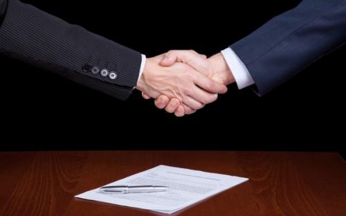 Мужчины подписывают устав ООО и жмут друг другу руки