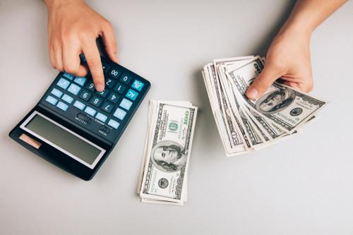 Мужчина на калькуляторе считает деньги, доллары