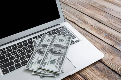 Заработанные деньги, доллары лежат на ноутбуке