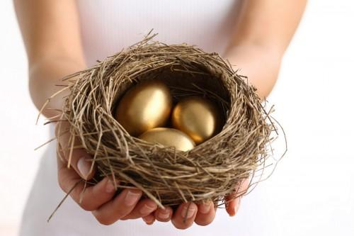Девушка держит в руке птичье гнездо с золотыми яйцами