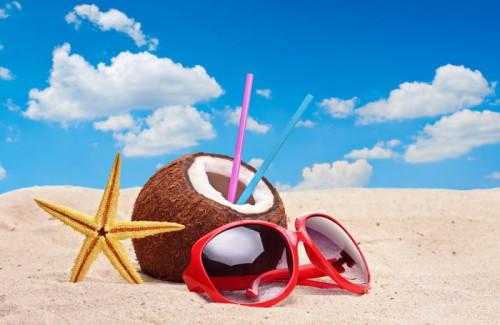 Морская звезда, очки, кокос лежат на песчаном пляже на берегу моря