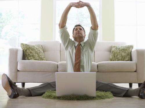 Мужчина сидя за ноутбуком ищет способы, как заработать на дому своими руками