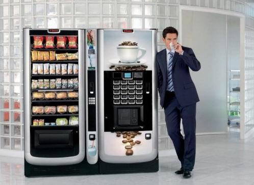 Мужчина в костюме пьёт кофе у кофейного вендингового автомата