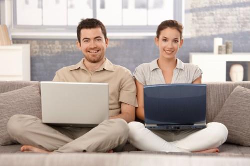 Мужчина и женщина сидят на диване с ноутбуками в руках