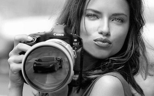 Красивая девушка фотографирует автомобиль на фотоаппарат Кенон