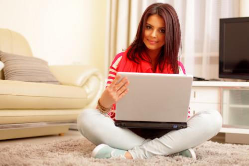 Девочка с помощью ноутбука ищет способы заработка на буксах