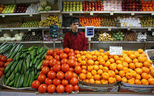 Продавец на рынке продаёт овощи и фрукты