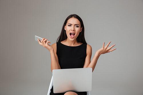 Возмущённая девушка за ноутбуком