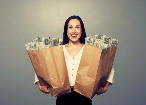 Женщина держит в руках пакеты с долларами