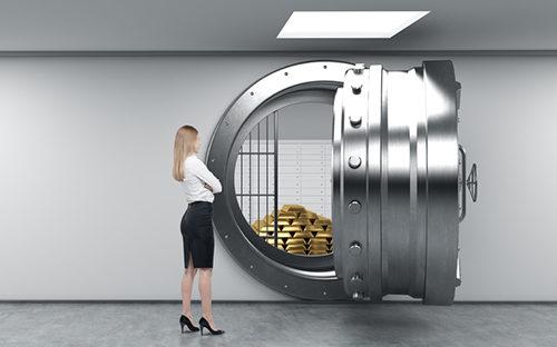 Девушка стоит у банковского сейфа