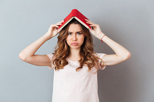 Девушка выпускник с книгой на голове