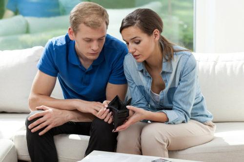 Муж и жена держат в руках пустой бумажник