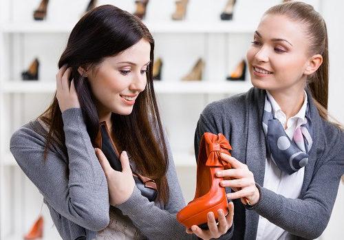 Девушка продавец презентует обувь покупателю