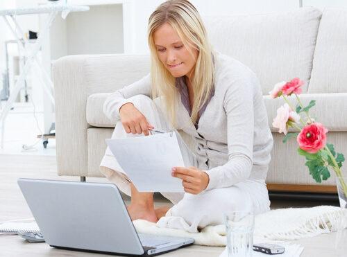 Девушка сидит на полу напротив ноутбука и смотрит на лист бумаги