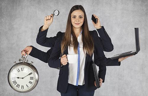 Девушка в деловом костюме держит в руках рабочие инструменты